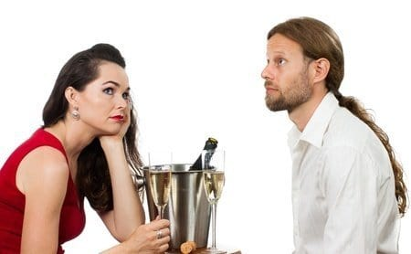 Bored couple drinking champagne